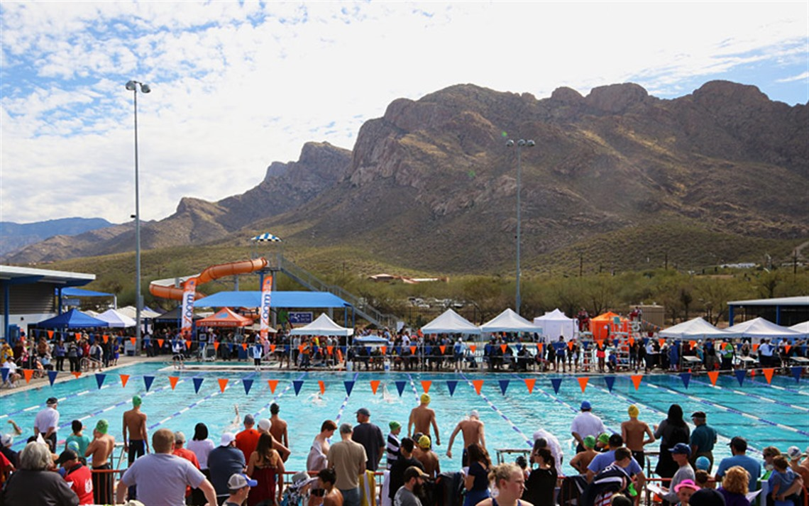 Wide shot of participants and attendees at 2018 Age Group State Championship at Aquatic Center with competition pool and Pusch Ridge mountain in background