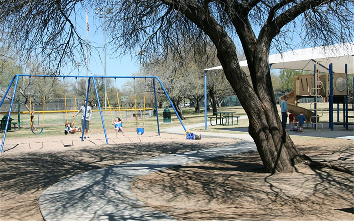 Kids playing on swings and playground equipment beneath shade of tree at James D. Kriegh Park
