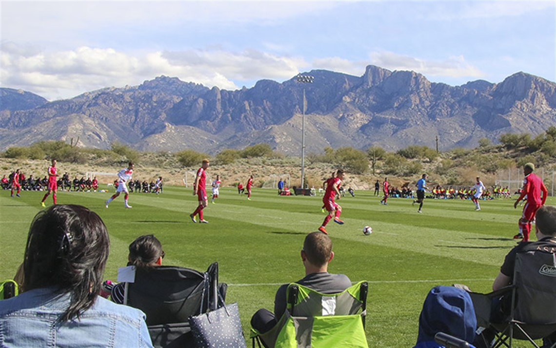 Spectators watching soccer game at Naranja Park with Catalina Mountains in background