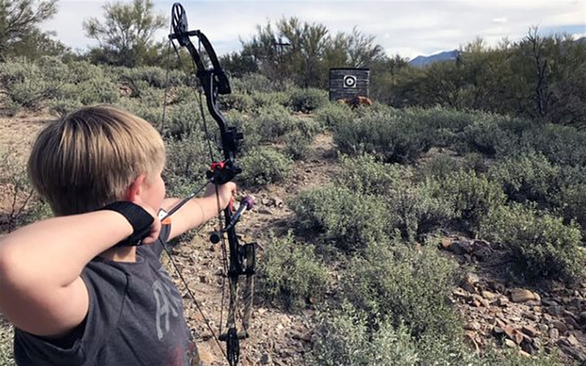 Youth aiming arrow at target with desert foliage in background