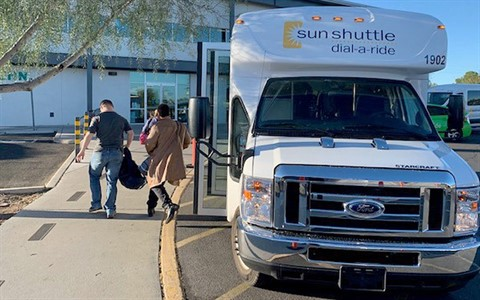 Sun Shuttle van drops off passengers in front of building
